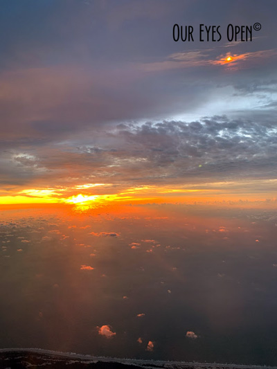 Rays of the sun reflect through the clouds high in the sky while on a jet plane.