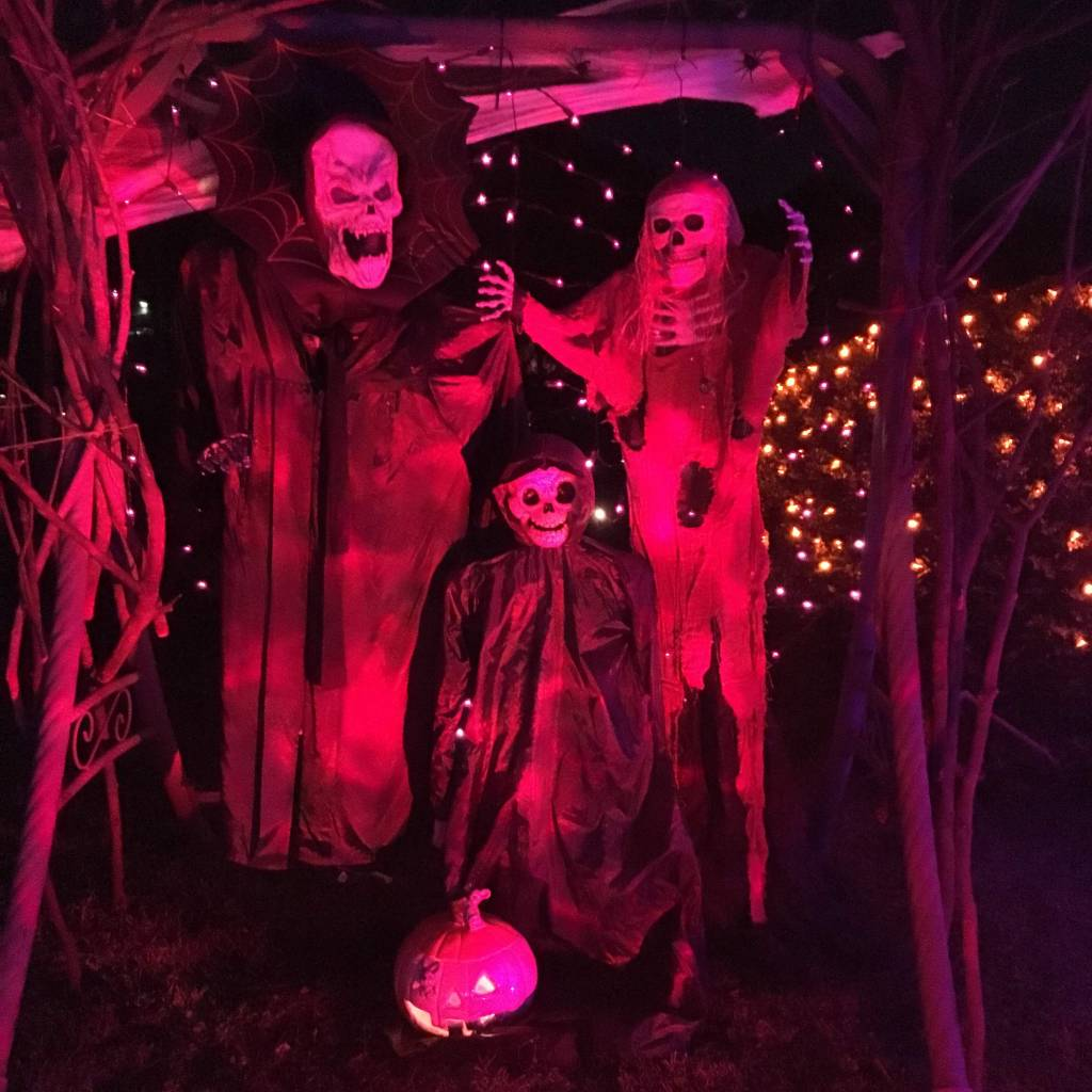 Skeleton family photo booth lit up by rotating orange lights.