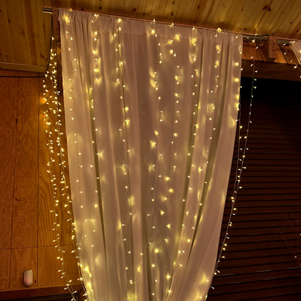 White miniature lights hanging from drapes as decorations for a wedding.
