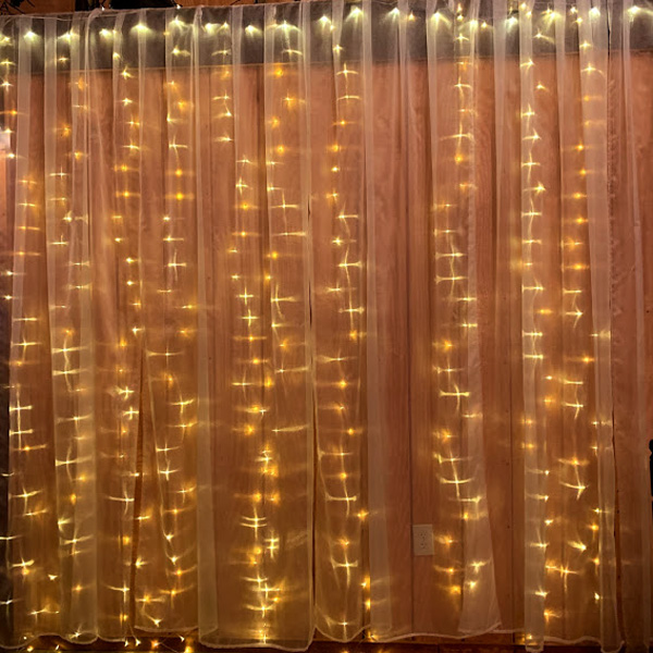 White miniature lights hang in straight lines from drapes for a wedding.
