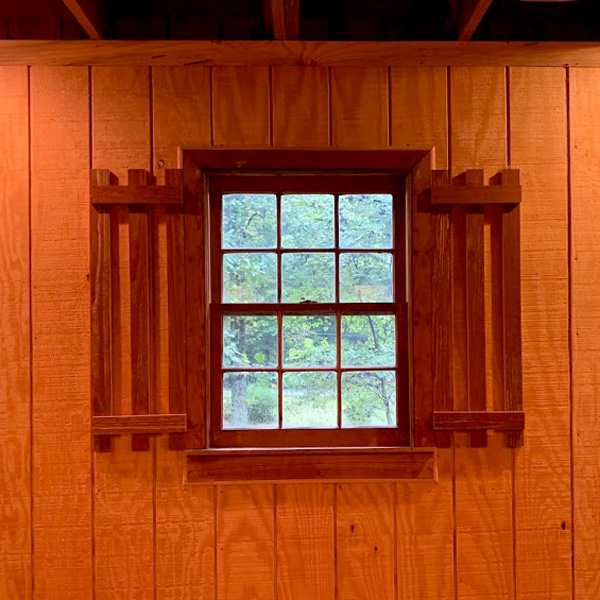 Framed Window with Square panes against Cedar Panel Walls.