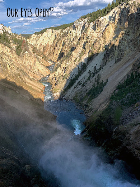 Mist forms as the water drops from the fall line at the Lower Falls in Yellowstone National Park in the Grand Canyon.