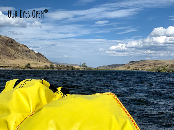 With the dry bag in the foreground and the mountains on either side of us paddling the Yellowstone River.