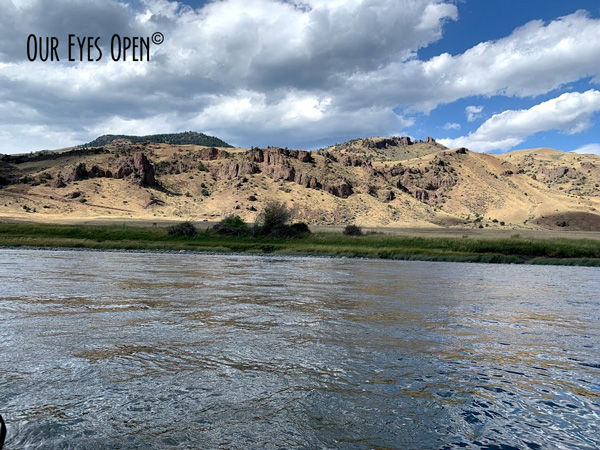 Clouds cast shadows on the Yellowstone River with the mountains in the background.