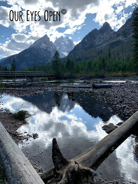 Cloud over in front of blue skies shading the sun giving us a perfect reflection with low water levels at the edge of String Lake in Grand Teton National Park.