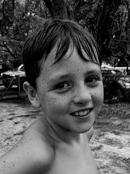 My grandson at a waterslide birthday party. His face is covered in freckles.