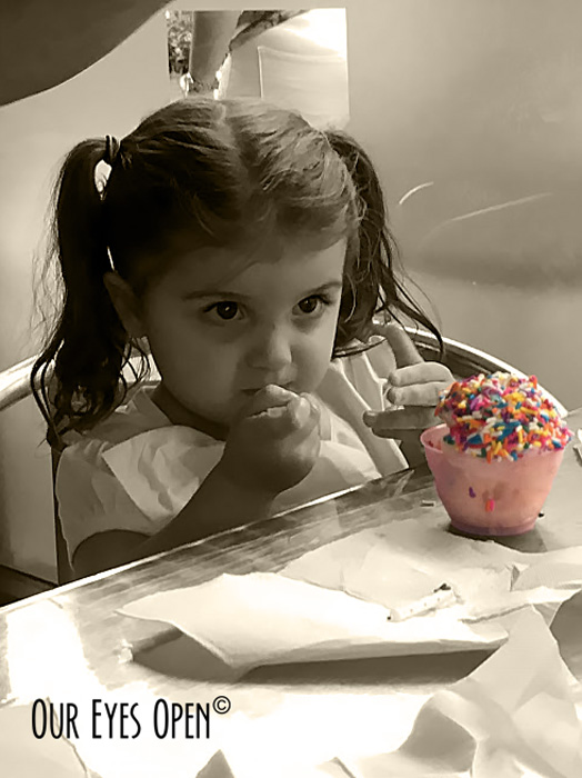 My youngest granddaughter having a birthday gelato covered in colorful sprinkles.