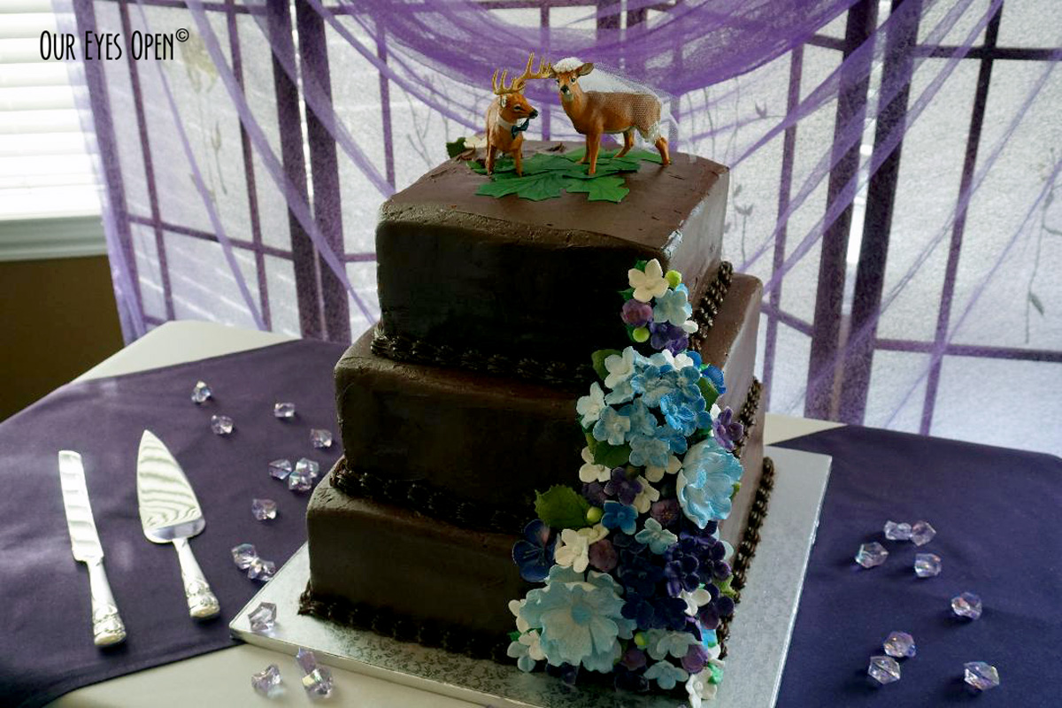 Chocolate wedding cake with blue flowers & buck and doe topper.