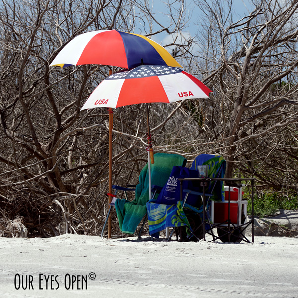 MacGyver rigged umbrellas for shade with our beach chairs, cooler and table on Little Talbot Island State Park beach in Jacksonville, Florida.