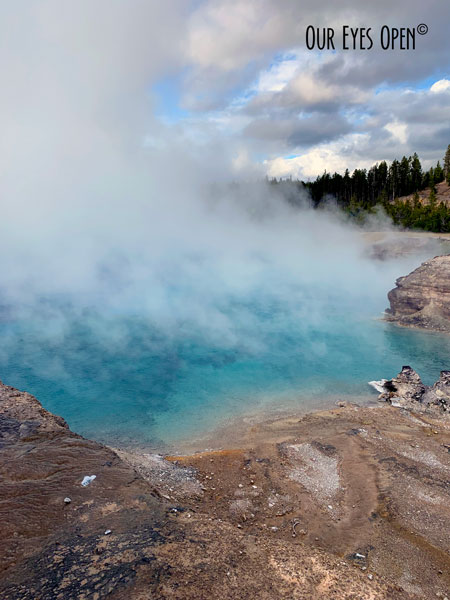 Turquoise water with a cloud of steam coming off one of the geysers in Yellowstone National Park.