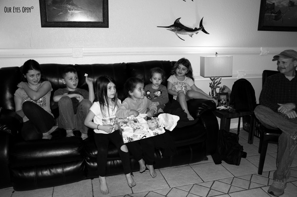 Grandkids gathered on the couch awaiting their Christmas presents.