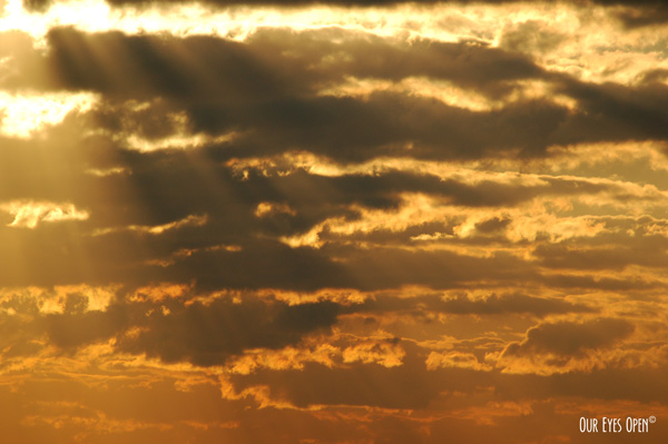A sunray beams through broken gray clouds presenting orange and yellow prism of color.