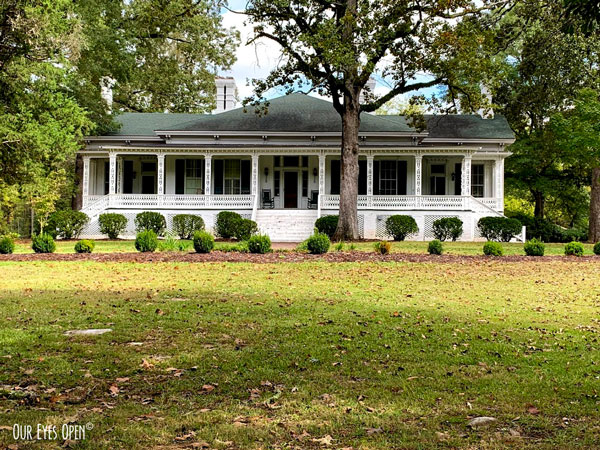 Large white house with a beautiful front porch on a large plot of land in Georgia.