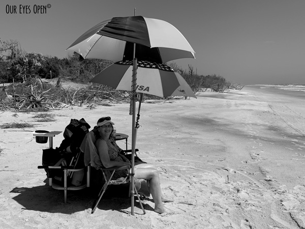 Me sitting on the beach at Little Talbot Island State Park under two umbrellas.
