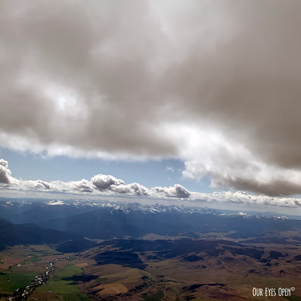 Photo taken from the seat of an aircraft over Montana, with the snow peaked mountains in the background and bright fluffy clouds in the foreground.