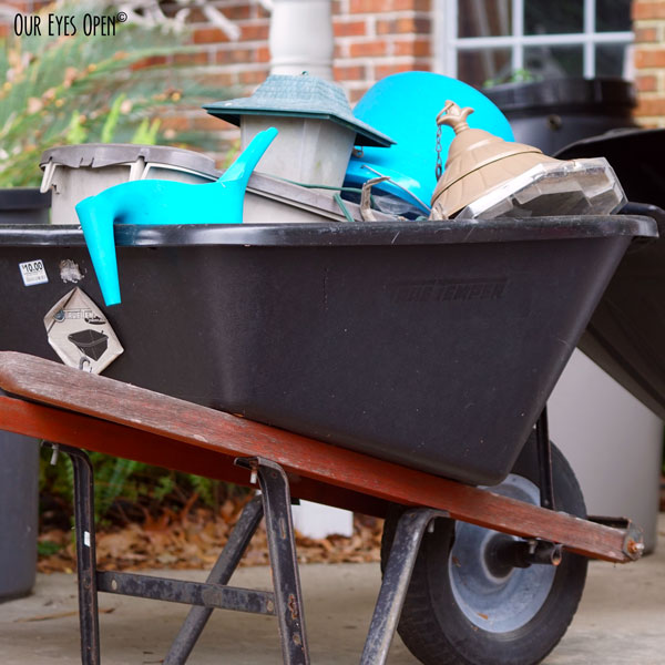 Wheelbarrow filled with bird feeders, a bright blue watering can and bright blue bucket.