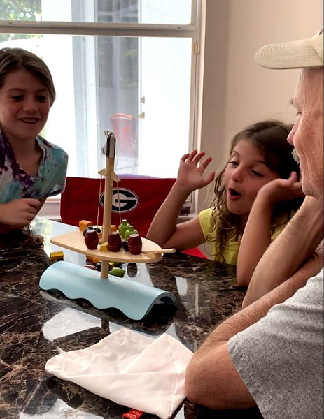 Two granddaughters playing a balance game.  It is a wooden ship with 25 pieces.  5 pieces of different cargo items are light and heavy weighted. Roll the dice to see what you have to mount on the boat without tipping it over.