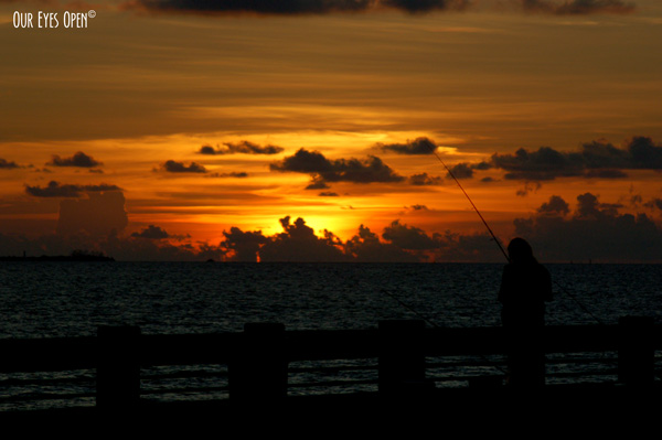 Someone fishing off the Skyway Bridge fishing pier in St. Petersburg, Florida with a beautiful orange, brown and gray sky sunset in the background.