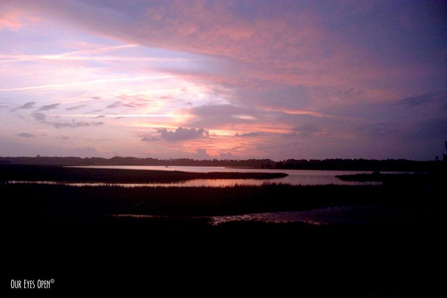 A sun moving towards the horizon at sunset overlooking the salt marsh in Jacksonville, Florida.