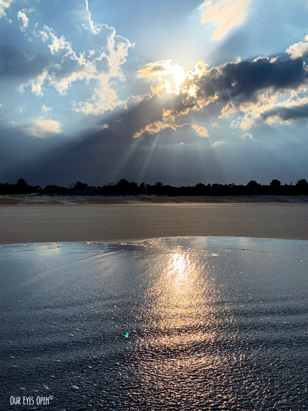 Sunrays blast from the clouds just above the sandy beach giving off a beautiful reflection in the water at Little Talbot Island State Park.